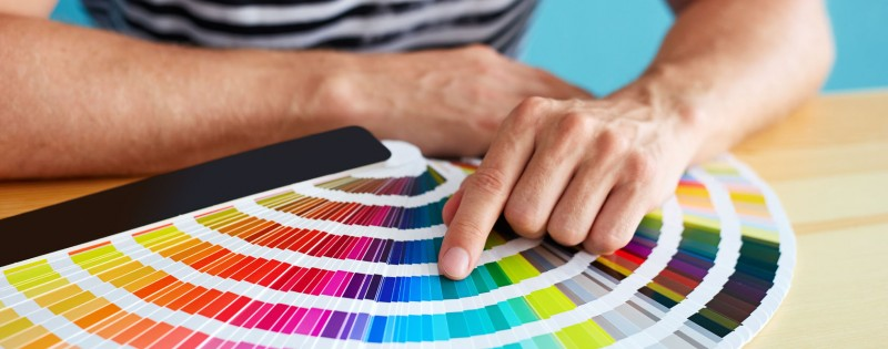 43778616 - graphic designer choosing a color from the sampler